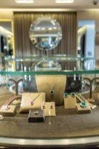 Collares, aretes y anillos en color verde y rosa dentro de una vitrina