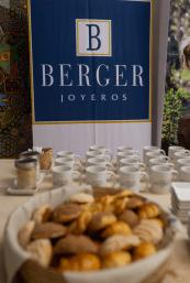 Mesa con panecillos, tazas y platos y al fondo un estandarte de Berger Joyeros
