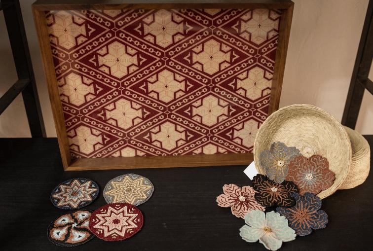 Figuras redondas y en forma de flor elaboradas con chaquira sobre una mesa