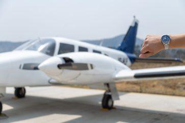 Mano de un hombre con el reloj plateado con caratula azul y al fondo un avión en blanco con azul