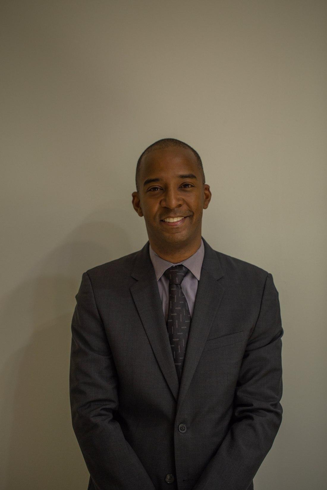 Dwayne Grannum con saco y corbata en negro y camisa azul de frente sonriendo