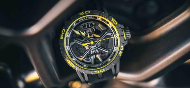 Reloj en tono gris con detalles en amarillo y plateado
