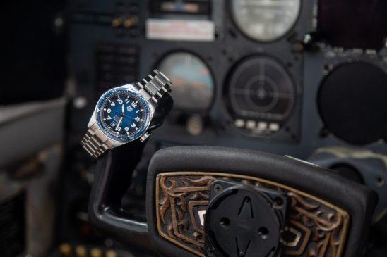 Reloj en color plateado con caratula en color azul con negro sobre el volante de un avión