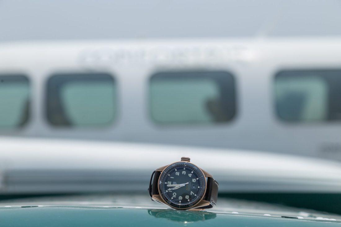 Reloj con correas negras y caratula dorada sobre el ala de un avión en color blanco con verde