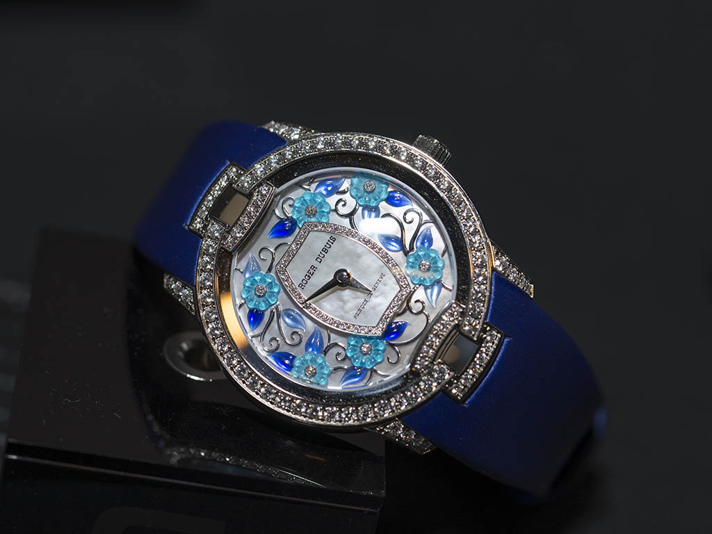 Reloj con correas azules con diamantes en la caratula y detalles de flores en diferentes azules