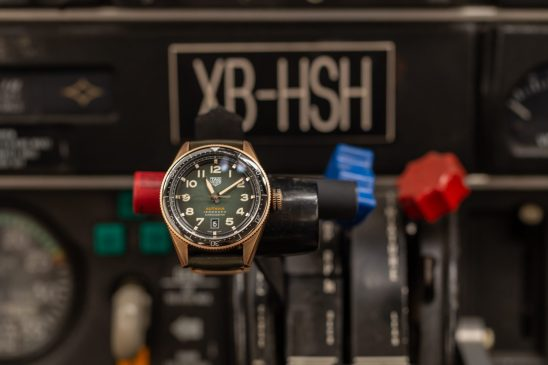 Reloj con correas negras y cartaula dorada sobre una palanca de un avión
