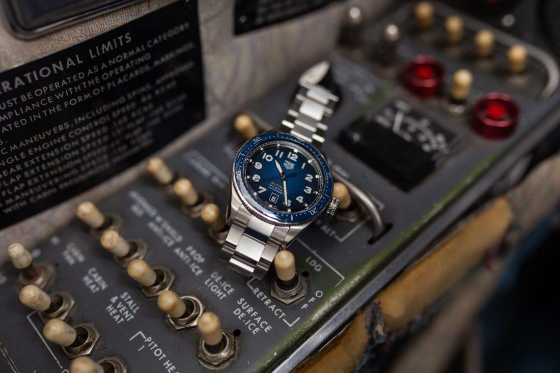 Reloj plateado con caratula azul sobre el panel de un avión