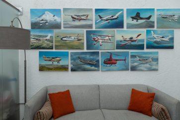Sala de espera con sillón gris y cojines naranjas y cuadros colgados en la pared de diferentes aviones