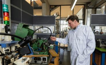 Stephen con bata blanca junto a una maquinaria de relojería