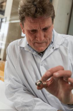 Stephen Forsey con bata blanca sosteniendo una pieza de reloj con su mano