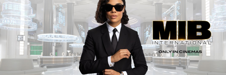 Tessa Thomspon con blusa blanca y saco, corbata y lentes en color negro con el cabello corto