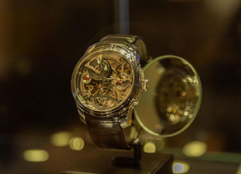 Reloj con correas doradas y caratula dorada con pequeños detalles rojos
