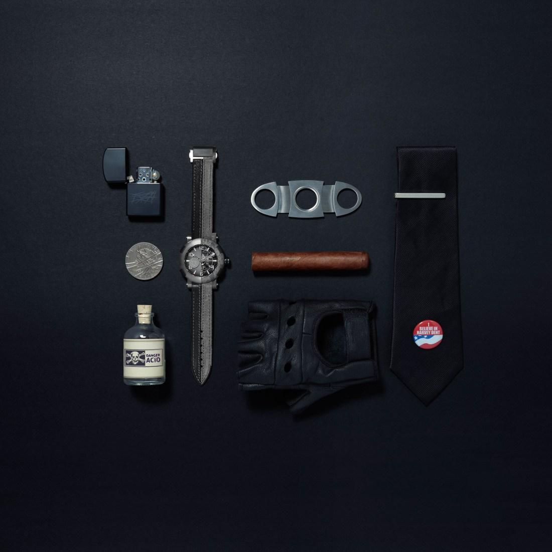 Encendedor, botella de ácido, reloj, guante, puro y corbata sobre una mesa negra
