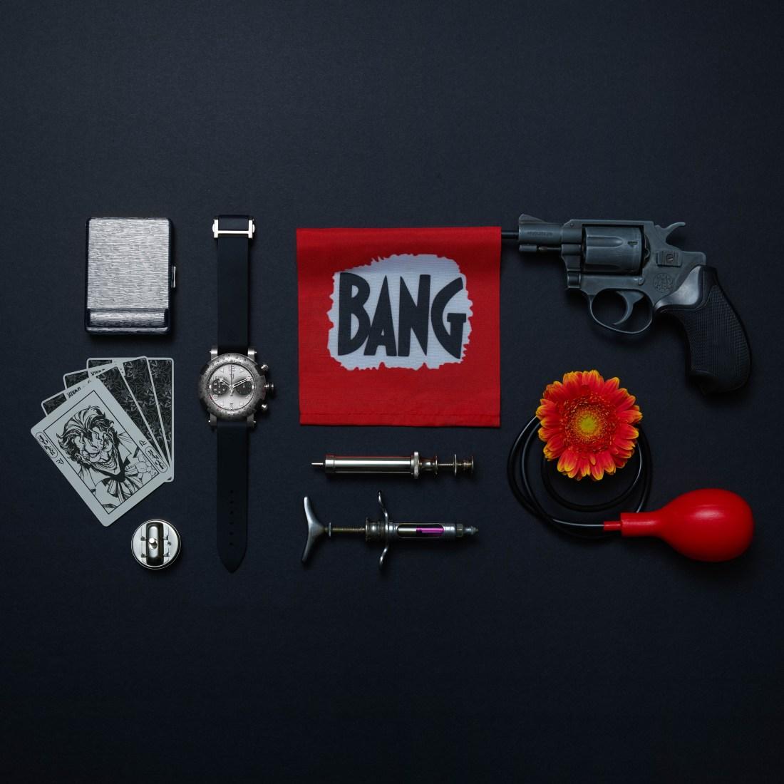 Reloj, cajetilla, cartas, pistola, jeringas y flor sobre una mesa negra