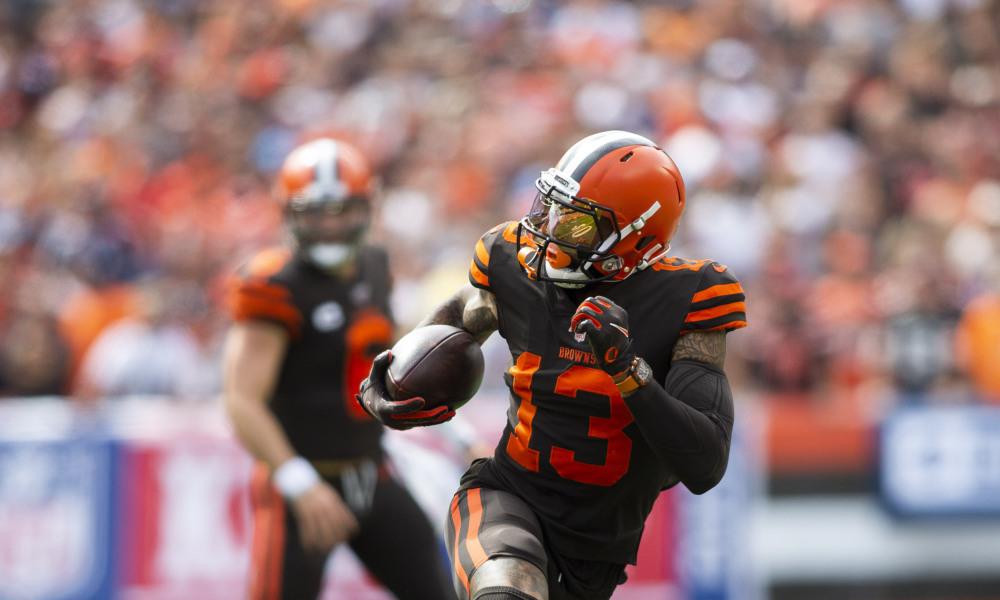Odell Beckham Jr con estimenta de jugador americano en color negro con naranja y casco naranja