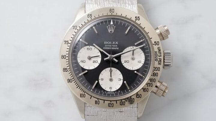 Rolex Daytona con correas blancas, caja beige y dial negro con esferas blancas
