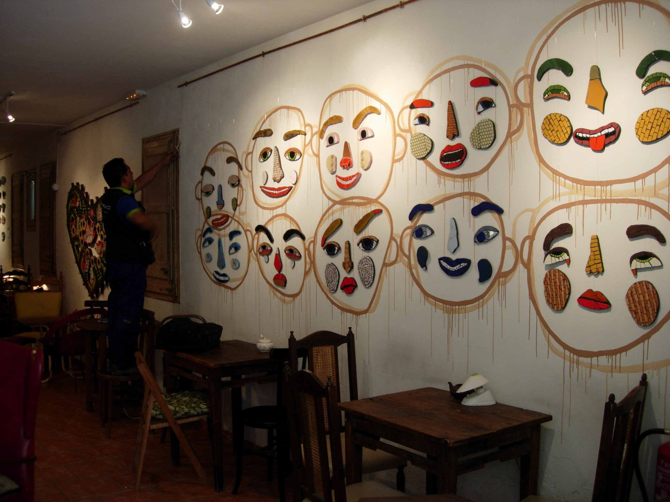 I love this installation -- painted directly on the walls, and the mosaic pieces hung to complete the faces.