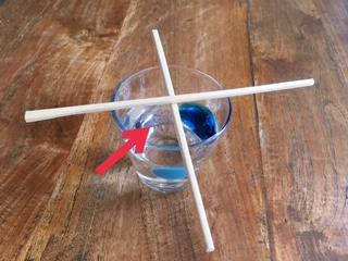 a glass of water with chopsticks