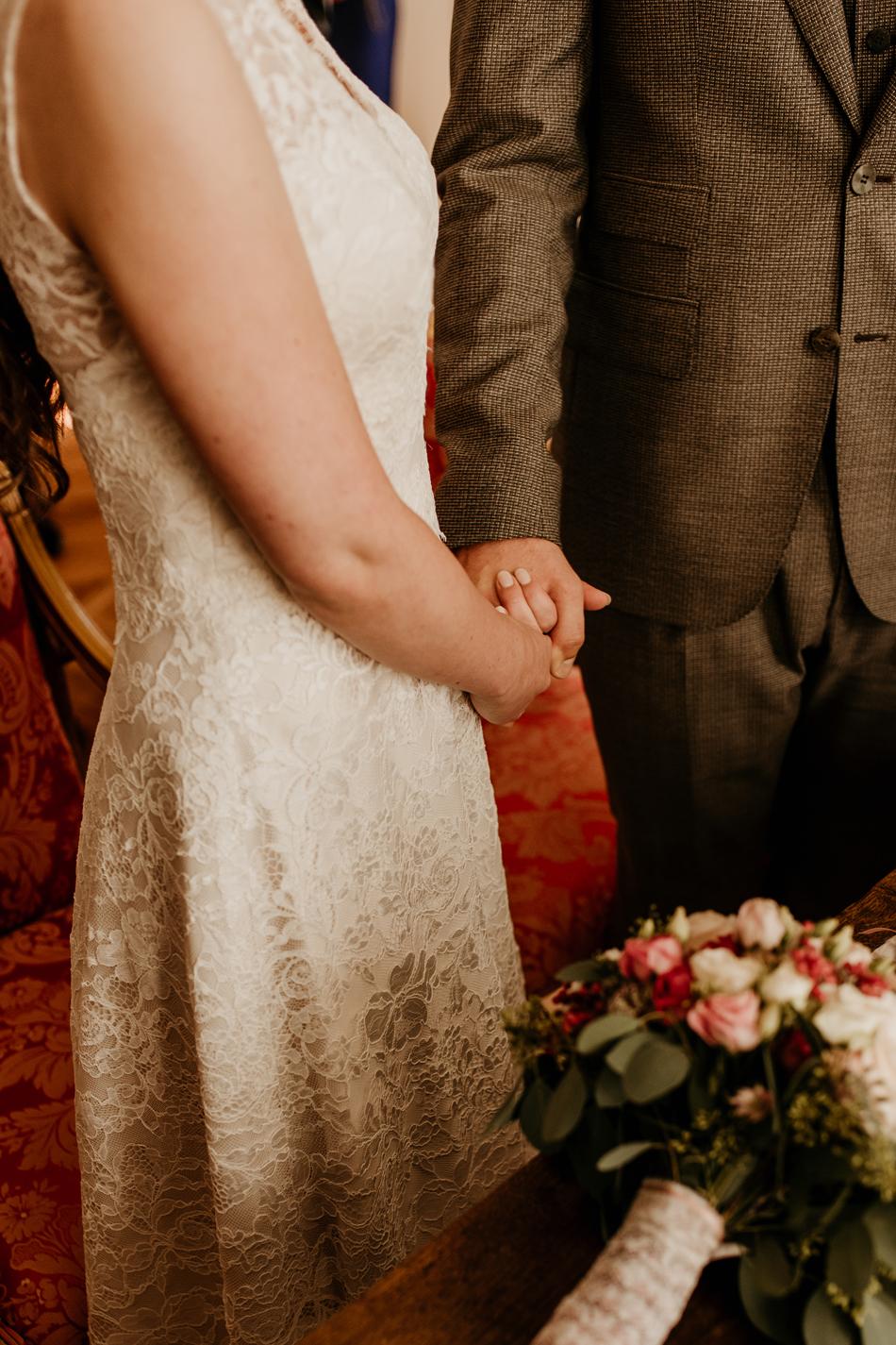 Brautpaar hält sich die Hände während der Trauzeremonie im Schloss Glücksburg