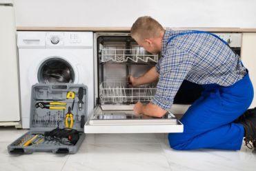 Мастер устанавливает посудомойку