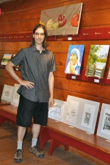 Portrait artist Anthony Galati with his art on the porch