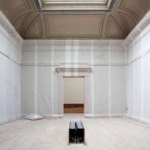 Een lege museumzaal. De vloer is bedekt met OSB-platen, de muren met plastiek foam. Binnenkort worden immers zowel het dak als de kroonlijsten in deze zaal afgebroken als voorbereiding op de bouw van het verticale museum.
