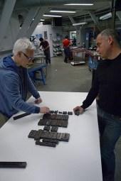 Tom en Herman zetten de lettercompositie (die ze straks zullen drukken) op een tafel uit.