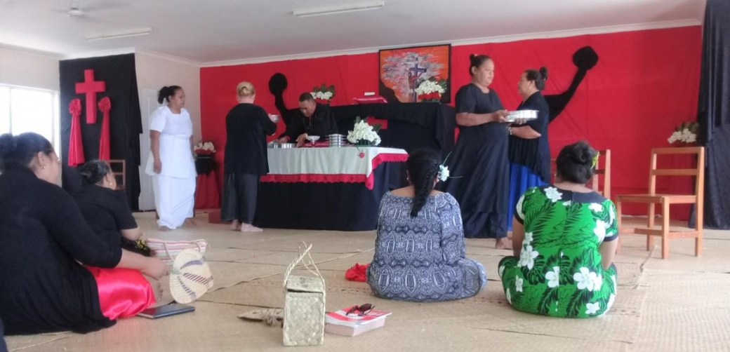 Rev Falani administering the Holy Communion and Mrs Sopoaga is in white dress