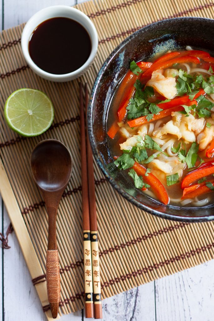 bowl of prawn pho on a straw mat with chop sticks