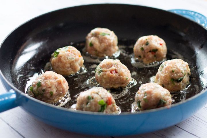 turkey Italian meatballs sizzling in a frying pan