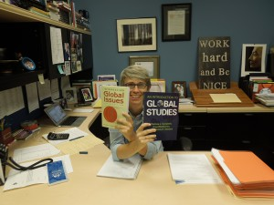 Ms. Anderson poses with textbooks that will be used in her Global Issues class this fall.