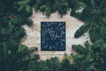green christmas decor with new year greetings (by annie spratt on unsplash)