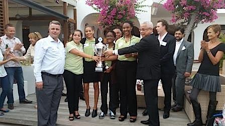 Minister President Marcel Gumbs reikt de trofee uit aan het winnende team. Links coach Roy Moes | Foto: Hilbert Haar