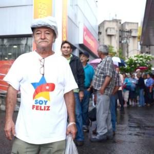 Man met t-shirt 'ik ben gelukkig' (soy feliz) wacht in de rij voor de supermarkt. foto: Sytske Jellema