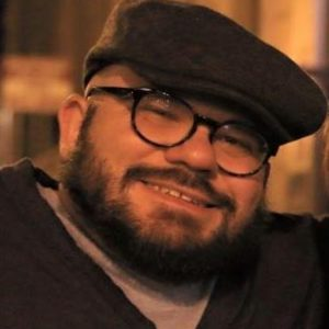 A portrait photo of Joe Stramondo. He is a white man with a brown beard wearing glasses, a brown cap, and brown v-neck sweater with a t-shirt underneathand smiling.