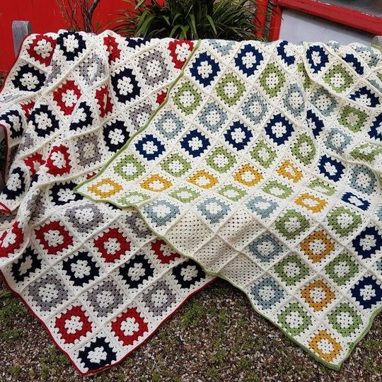 Two skillfully made crocheted blankets displayed on a bench