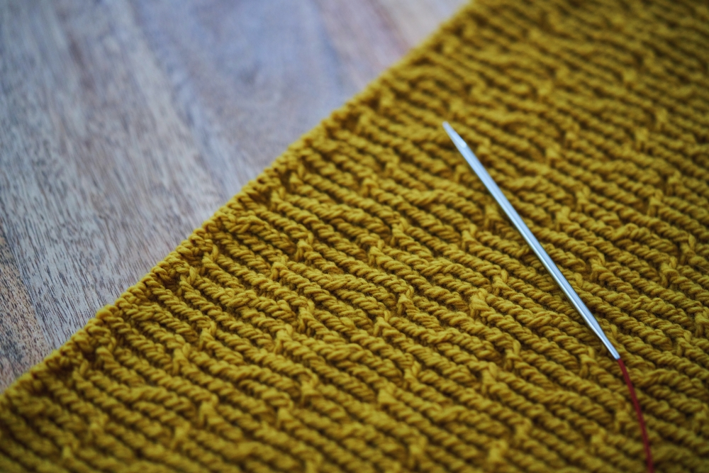 closeup of cable knitting with golden yellow yarn