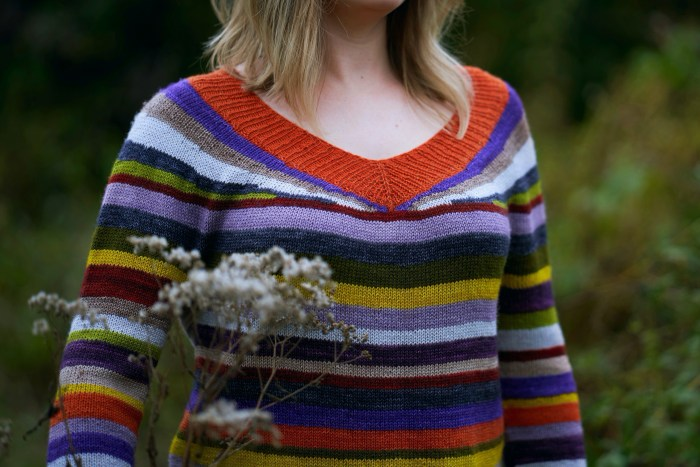 A closeup of a v-neck striped sweater knit in orange, green, purple, yellow and gray colors