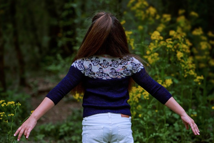 A girl wears a dark blue hand knitsweater with a whitish yoke that features dark blue butterfly motifs. Her back is facing, and her arms are spread out.