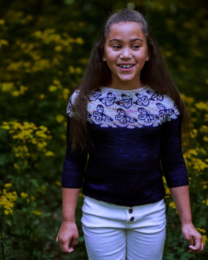 A smiling girl wears a dark blue hand knit sweater with butterfly motifs in the yoke.