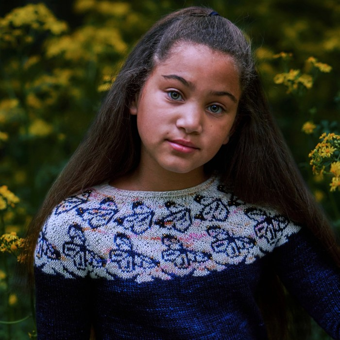A girl wears a dark blue hand knitsweater with a whitish yoke that features dark blue butterfly motifs.