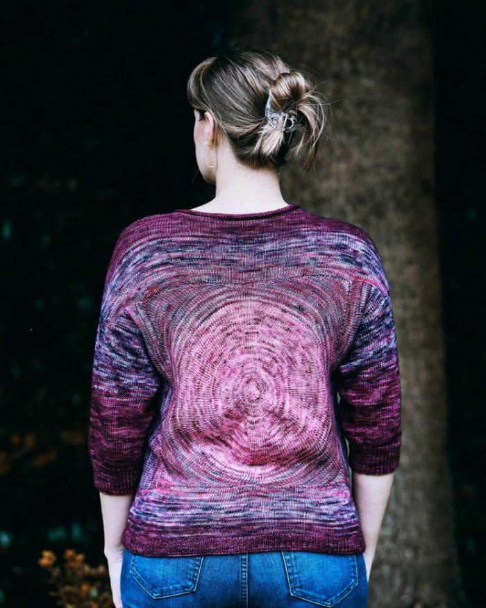 A woman has her back to the camera and is wearing a handknit sweater that fades radially from pinkish purple to dark wine.
