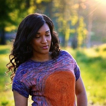 A woman gazes downward with the sun rays angled in from her left. She is wearing a handknit tee featuring an orange middle that fades into pink and then purple.