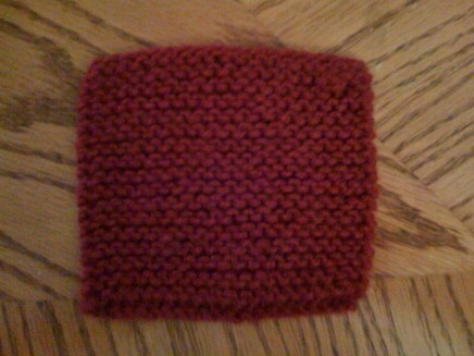 Before blocking, this square is noticeably shorter than it is wide, and mostly opaque, as it is off the needle.