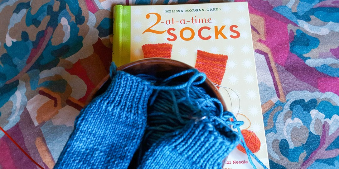 Socks knitted two at a time on yarn bowl with book