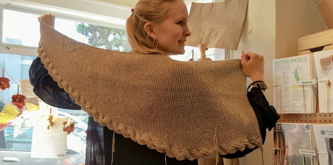 Unfinished knitted shawl held up across shoulders