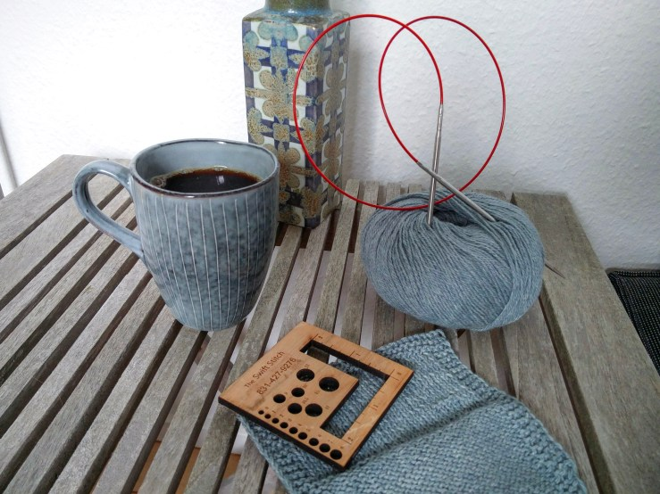 Dusty blue ball of yarn, swatch and coffee mug