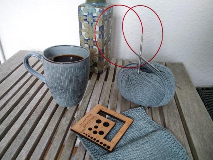 Dusty blue ball of yarn, swatch and coffee mug