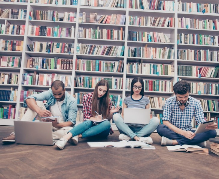 Students sitting on floor in front of bookshelves