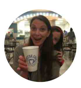 Jodi holding a cup of coffee with Dagny peeking out from behind her head.